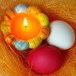 Candle and eggs  in a small nest — Stock Photo