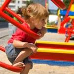 Little girl on playground equipment — Stock Photo