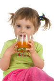 Cute little girl drink carrot juice — Stock Photo