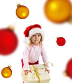Cute girl with a xmas gift and spheres — Stock Photo