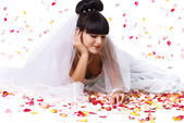 Beautiful bride and rose petals — Stock Photo