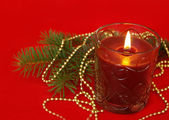 Candle and decoration on red — Stock Photo