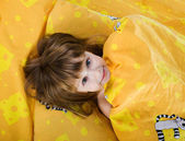 Cute little girl on the bed — Stock Photo