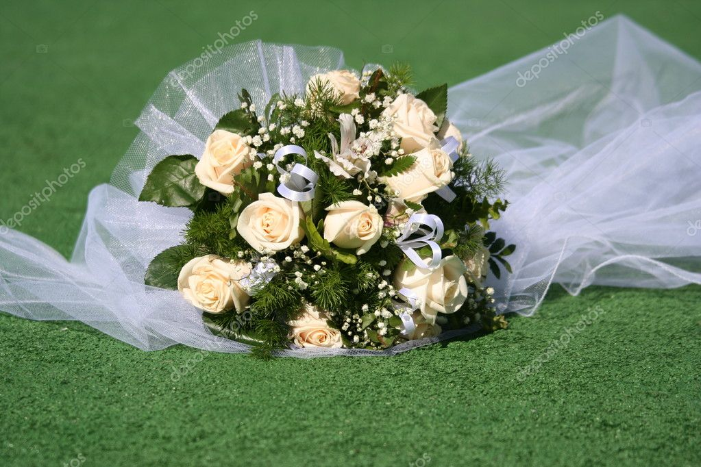 There is a beautiful bridal bouquet the bride and bridal veil.  Stock Photo #1095279