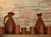 Clay jugs and cups on a shelf — Stock Photo