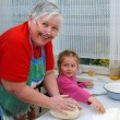 Stock Photo: Grandmother and granddaughter knead the