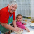 Royalty-Free Stock Photo: Grandmother and granddaughter knead the