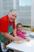 Grandmother and granddaughter knead the — Stock Photo