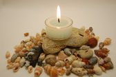 Stones, a lot of small shells and candle — Stock Photo
