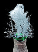 Bottle and water splash on black — Stock Photo