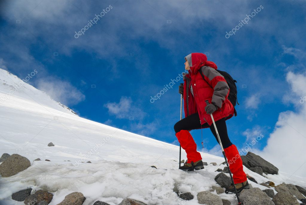 Young, beautiful girl alpinist  in a red jacket and with ski sticks rises uphill on white snow  Stock Photo #1095446