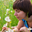 Beautiful, young girl and dandelion — Stock Photo