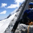 Stock Photo: Mountaineer sits on a rock