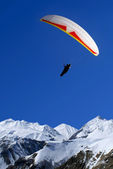 Paraglider flies above mountains — Stock Photo