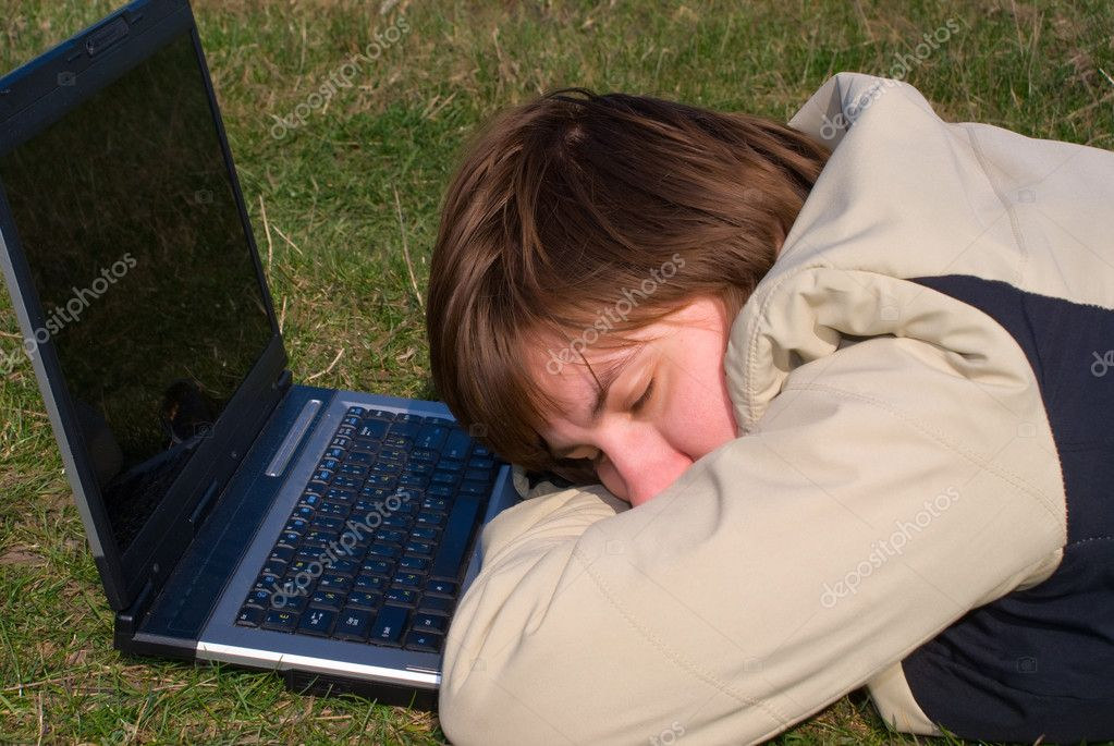 A young beautiful girl fallen asleep on the exposed notebook, standing on a green grass — Stock Photo #1191544