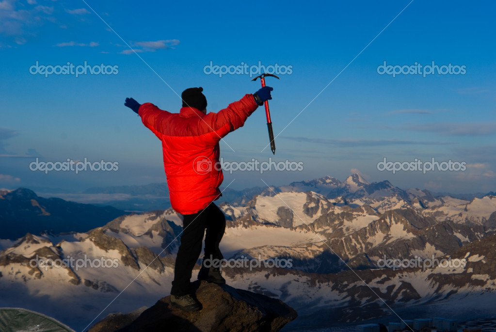 Mountaineer  in red jacket with an ice-axe in  hand looks at mountain landscape — Stock Photo #1192297