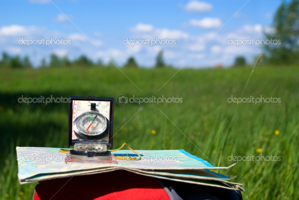 Compass and map lie on  backpack on  background beautiful nature — Stock Photo #1192796