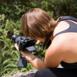 Stock Photo: Girl takes pictures an agrimony