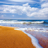 Sandy shore and white clouds on blue sky background. — Stock Photo