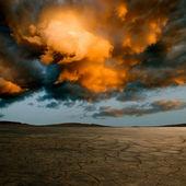 Désert de sol fissuré et nuages dramatiques. — Photo