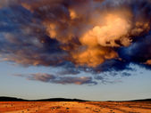 Dark clouds over stony desert. — Stock Photo