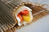 Rolled pancake with fruits — Stock Photo