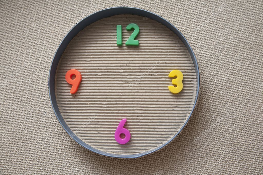 Toy clock made from magnetic digits in a round paper box cover — Lizenzfreies Foto #2248373