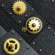 Gold gears against ferrous metal - Stock Photo
