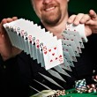 Man skilfully shuffles playing cards - Stock Photo