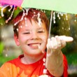 Stock Photo: Boy under an umbrella during a rain