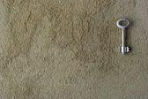 Iron key on a concrete wall — Stock Photo