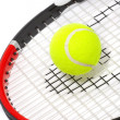 Tennis racket with a ball on a white bac — Photo