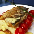 Fish with tomatoes and a potato - Stock Photo