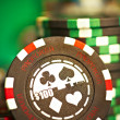Gambling chips on green cloth - Stock Photo