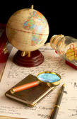 The globe, magnifier with a notebook and — Stok fotoğraf