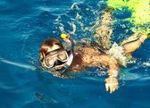 Boy floats in the sea — Zdjęcie stockowe