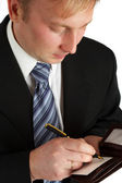 The businessman in a black suit signs a — Stock Photo