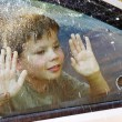 Child and window on a wet rainy day - Stock Photo