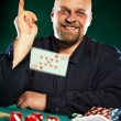 Man with a beard plays poker - Stockfoto