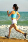 Girl runs along the sea... — Stock Photo