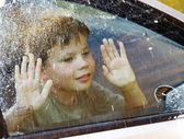 Child and window on a wet rainy day — Stock Photo