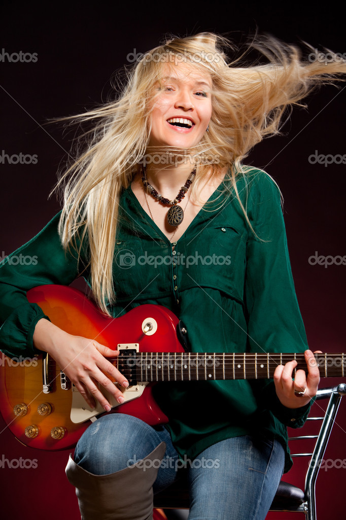 Girl with a guitar on a dark red background — Stock Photo #2372562