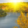 Golden autumn sunbeams above river and m — Foto Stock