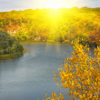Golden autumn sunbeams above river and m — Stock Photo