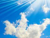 Raios de sol esplêndidos e nuvens no céu azul — Fotografia Stock