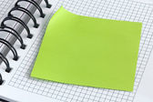 Notebook and green sticker — Stock Photo