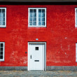 Red wall with white windows and door — Stock Photo