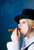 The woman in a hat smokes a cigar — Stock Photo
