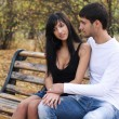 Couple sitting together on a bench - Stock Photo