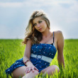 Beautiful woman sitting in the field — Stock Photo #1451956